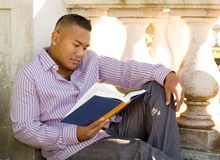 Man Reading. Asian Man Reading a Book Outdoors stock images
