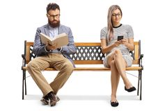 Free Man Reading A Book And Woman Sitting On A Bench And Typiing On A Mobile Phone Royalty Free Stock Photography - 160055887
