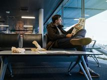 Man reading in airport THe New York Times magazine newspaper royalty free stock photo