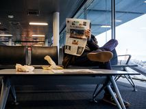 Man reading in airport THe New York Times magazine newspaper. BASEL, SWITZERLAND - NOV 11, 2017: Businessman in casual clothes reading the New Yourk Times royalty free stock image