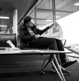 Man reading in airport THe New York Times magazine newspaper. BASEL, SWITZERLAND - NOV 11, 2017: Businessman in casual clothes reading the New Yourk Times stock image