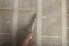 Man reading from an ancient torah scroll up close. Top view Royalty Free Stock Images