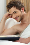 Man reading in bed Stock Photo