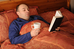 Man reading in bed. While holding a mug royalty free stock image