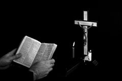 Man reading bible. Near prayer crucifix with candles burning, book is open to st. matthew Stock Photos