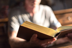 Man reading the Bible. In dim light royalty free stock photos