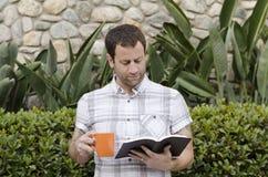 Man reading the Bible while holding an orange coffee mug. Stock Images