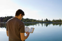 Man Reading Bible By Lake. Young man in front of lake reading the Bible (King James Version stock photo