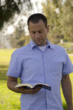 Man reading bible. Man reading a bible outside on a sunny day Royalty Free Stock Images