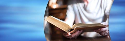 Man reading the bible; panoramic banner. Man reading the bible in dim light; panoramic banner stock photography