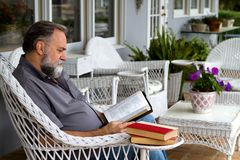 Man Reading Bible On Porch Royalty Free Stock Image