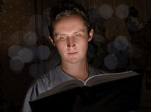 Man reading book. In darkness royalty free stock photo