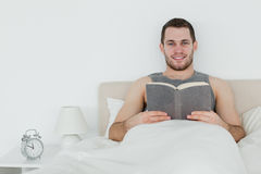 Man reading a book. In his bedroom Stock Images