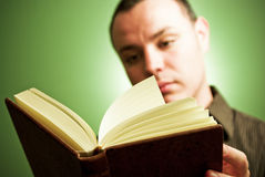 Man reading a book. Young man reading a book, against green background Royalty Free Stock Photos