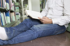 Man reading book in aisle in library Stock Photos