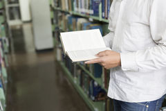 Man reading book in aisle in library Royalty Free Stock Images