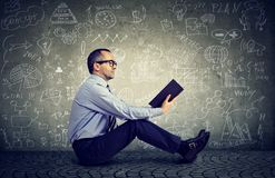 Man reading a book on a background with science formulas stock photo