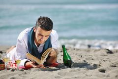 Man reading book at beach Royalty Free Stock Image