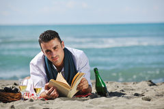 Man reading book at beach Royalty Free Stock Photos