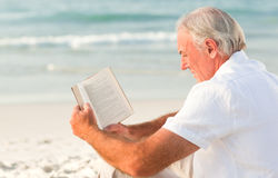 Man reading a book on the beach Royalty Free Stock Images