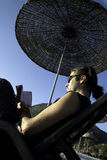 Man reading a book on beach. Man sunbathing and reading a book on tropic beach Royalty Free Stock Image