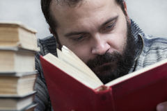 Man reading book. A bearded man with a red book, reads Royalty Free Stock Photo