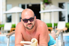 Man reading a book. Beautiful muscular man  reading a book on the pool of   luxurious hotel Royalty Free Stock Images