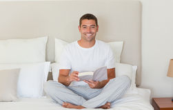Man reading a book on the bed Stock Photo