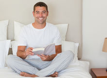 Man reading a book on the bed Stock Photos