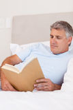 Man reading book in bed Stock Image