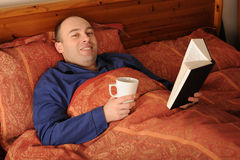 Man reading book in bed Royalty Free Stock Images