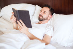 Man reading a book in bed. Attractive young man with a beard relaxing in his bed and reading a book in the morning Stock Photos