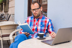 Man is reading a book in cafe. He is drinking coffee. Stock Image
