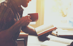 Man reading book with coffee or tea Royalty Free Stock Image