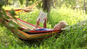 Man reading the book in cozy hammock under the trees shadows stock video footage