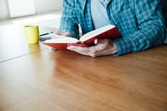 man reading book with cup of tea or coffee stock images