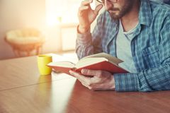 man reading book with cup of tea or coffee stock photos