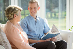 Man reading book with elderly woman stock images