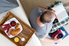 Man Reading Book and Enjoying Coffee and Breakfast stock photos