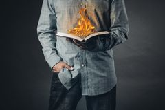 Man reading a book on fire. Reading concept. Christian concept for faith spirituality and religion with gray background stock photography
