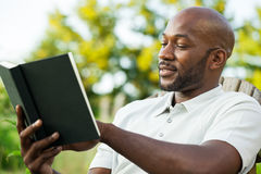 Man Reading Book. Handsome African American man in his late 20s reading a book at the park on a summer day Stock Images