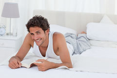 Man reading a book on his bed. At home Stock Images