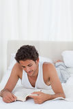 Man reading a book on his bed Royalty Free Stock Image