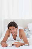 Man reading a book on his bed. At home Royalty Free Stock Photos