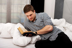 Man reading a book in his bed. Handsome man reading a book in his bed Royalty Free Stock Photos
