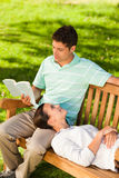 Man reading a book with his girlfriend. Lying down a bench Stock Image