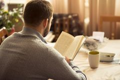 Man reading a book at his home. Young man enjoying a great piece of writing, a new bestseller, enjoying his hobby Royalty Free Stock Images