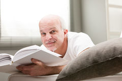 Man reading a book in his living room Royalty Free Stock Image