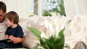 Man reading a book for his son. Sitting on the sofa stock footage