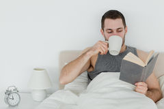 Man reading a book while holding a cup of coffee. In his bedroom Royalty Free Stock Photography